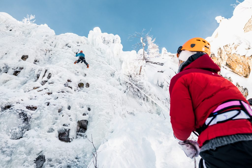 Climber climbing a wall of ice